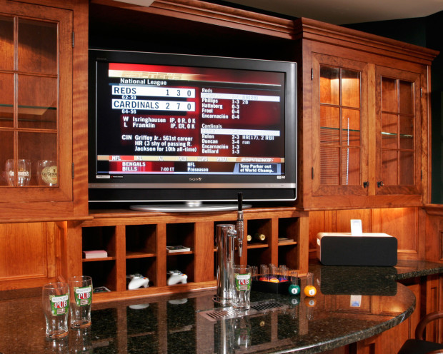 Home Game Rooms: Saratoga Springs general contractor Teakwood Builders designed and built this multi-function bar area. Custom cherry cabinets boast oil-rubbed bronze hardware, upper glass panels and discreet undercabinet lighting concealed by valance trim. Wine storage fits neatly beneath the television cabinet. Cut out of the granite countertop is a beer tap for the kegerator installed below.