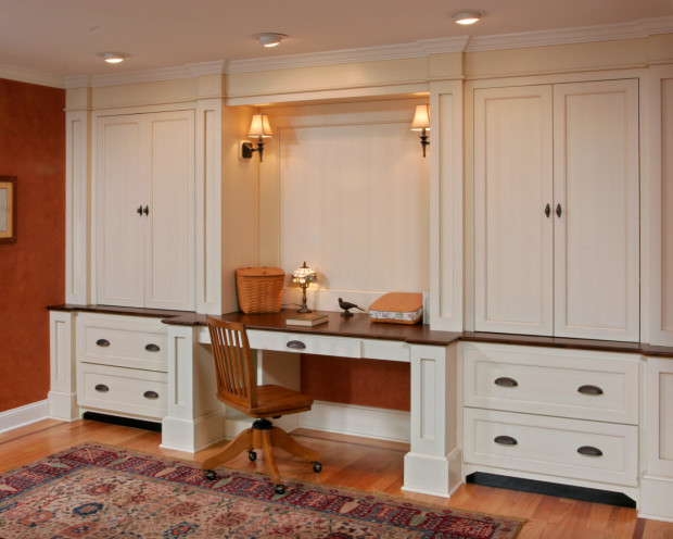 Teakwood designed and built this ample unit to serve as an attractive home office between the kitchen and great room. Deep drawers contain files, while upper cabinets conceal books and media components. Detailed millwork and furniture-like details help to integrate this unit into the nearby living spaces.
