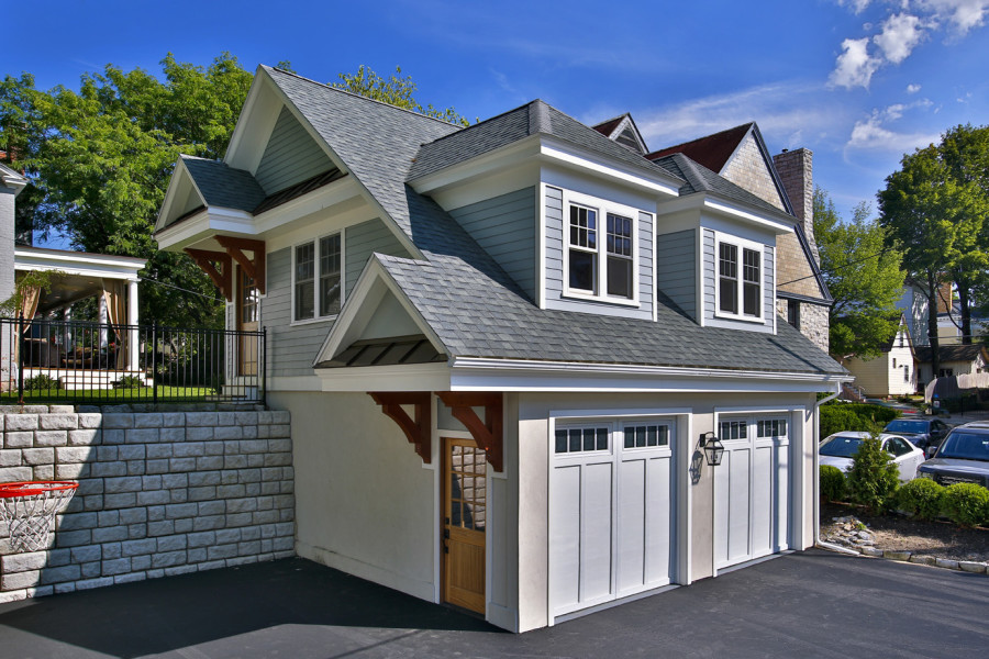 A stone retaining wall made it possible to build a multilevel two-car garage with room for a guest apartment upstairs. Timber brackets, a natural wood door, cedar siding and stucco bring the carriage house into historical concert with the home without directly mimicking the older materials.