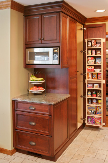 The custom millwork cabinetry created by Teakwood Builders for the microwave center has deep drawers for preparation and storage containers. The adjacent tall pantry cabinets make for easy grab-and-go food preparation.