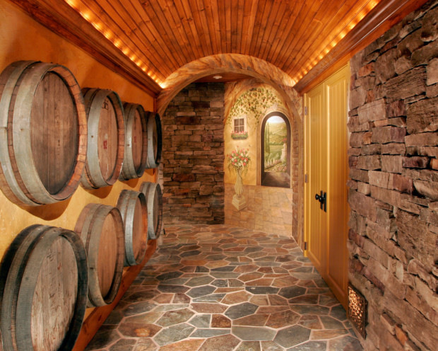 Home Game Rooms: A unique barrel-vaulted ceiling is illuminated by low-voltage accent lighting, concealed by tailored molding. Teakwood Builders repurposed wine casks as part of a decorative wall display wine cellar wall treatment.