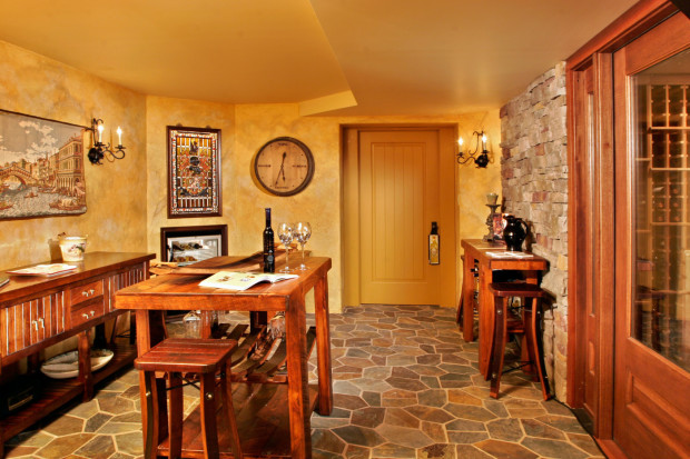 Home Game Rooms: A tasting room features cultured stone walls, natural slate floors, wrought-iron candle wall sconces and solid wood doors with hand-milled trims in Teakwood Builders' transformation of a Loudonville, NY, basement into a Tuscan wine cellar.