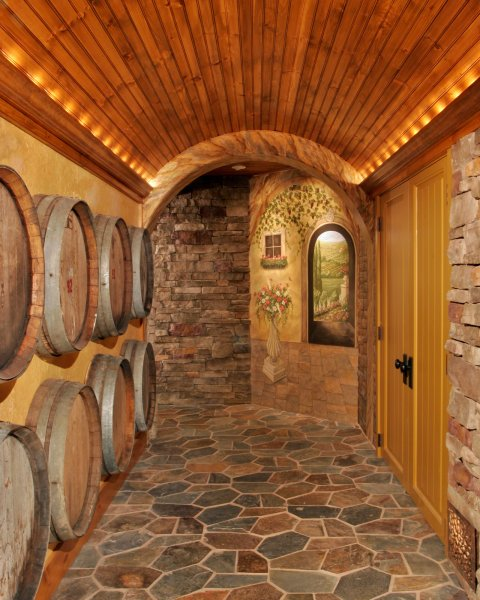 Vintage wine casks collected during the owners' travels were reclaimed and recycled in this one-of-a-kind wine cellar wall treatment in Teakwood Builders' renovation of a Loudonville, NY, basement into a Tuscan wine cellar.