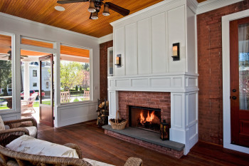 Rich, natural materials and finishes help this sitting porch fireplace comfortably maintain the character of this historic home year round. Teakwood Builders, kitchen and bath remodeler, custom home builder and general contractor Saratoga Springs and Capital Region