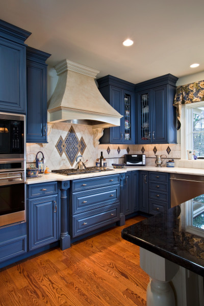 Traditional scrollwork on the hood and millwork below the range bring familiar visuals into an eclectic space. Kitchen design by Teakwood Builders, Saratoga Springs, NY.
