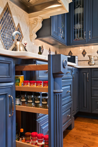 Custom millwork in this Saratoga Springs, NY, kitchen design keeps spices handy with a pullout rack that neatly disappears when not in use.