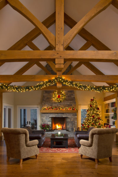 The fireplace and rustic beams add cozy warmth to the family room. Next to an eight-foot wide stone fireplace, French doors lead to a two-story screened porch overlooking the swimming pool, fields and trees.
