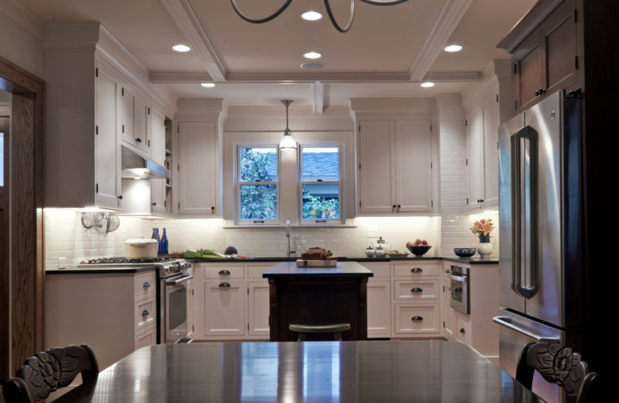 Clean lines and bright whites bring harmony into this u-shaped kitchen, while coffered ceilings and interesting lighting keep it modern and up to date.