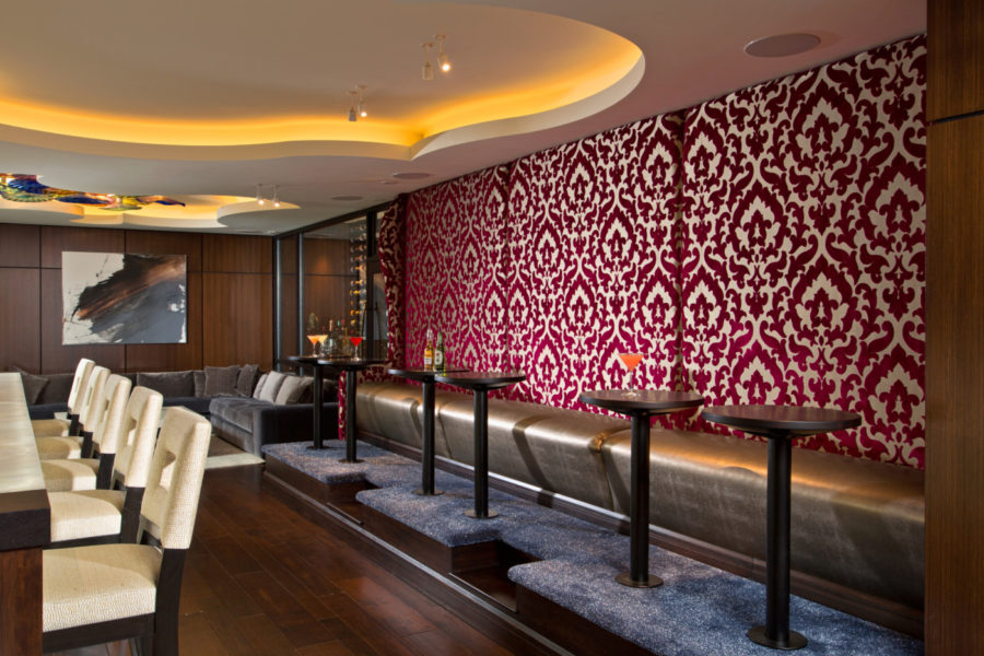 Gorgeous velvet damask wall fabric acts as a backdrop for the banquette area and provides additional seating for the bar. Painting by artist Zack Lobdell.