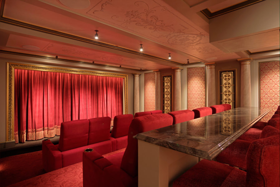 The cinema also includes a marble bar top with high seating to accommodate those with drinks or snacks. The red velvet curtain adds the final touch, parting to reveal the movie screen.