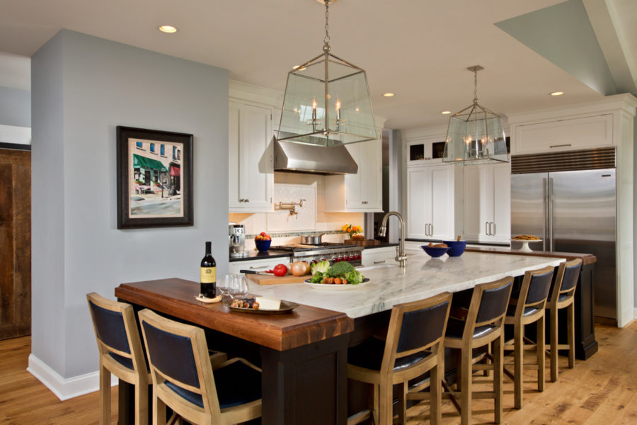 Showcased here is the impressive thirteen-foot island with Danby marble and walnut ends, seating up to seven. It allows ample space for food preparation. To the back right is the breakfast nook the family uses for everyday dining.