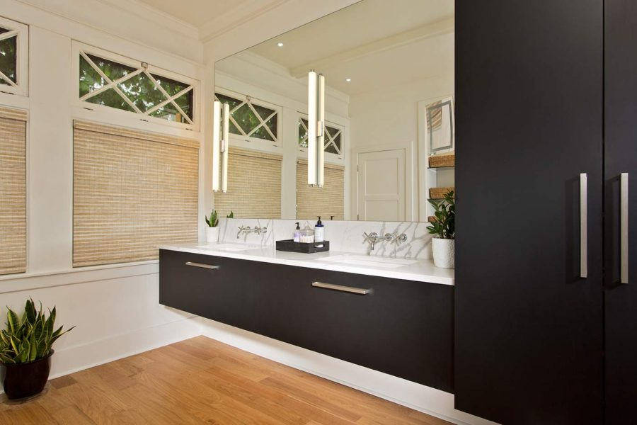 High contrast continues in the master bathroom, where Ebony cabinetry pops against the clean white countertops and walls. Transom windows allow for ample light in the space without compromising privacy.